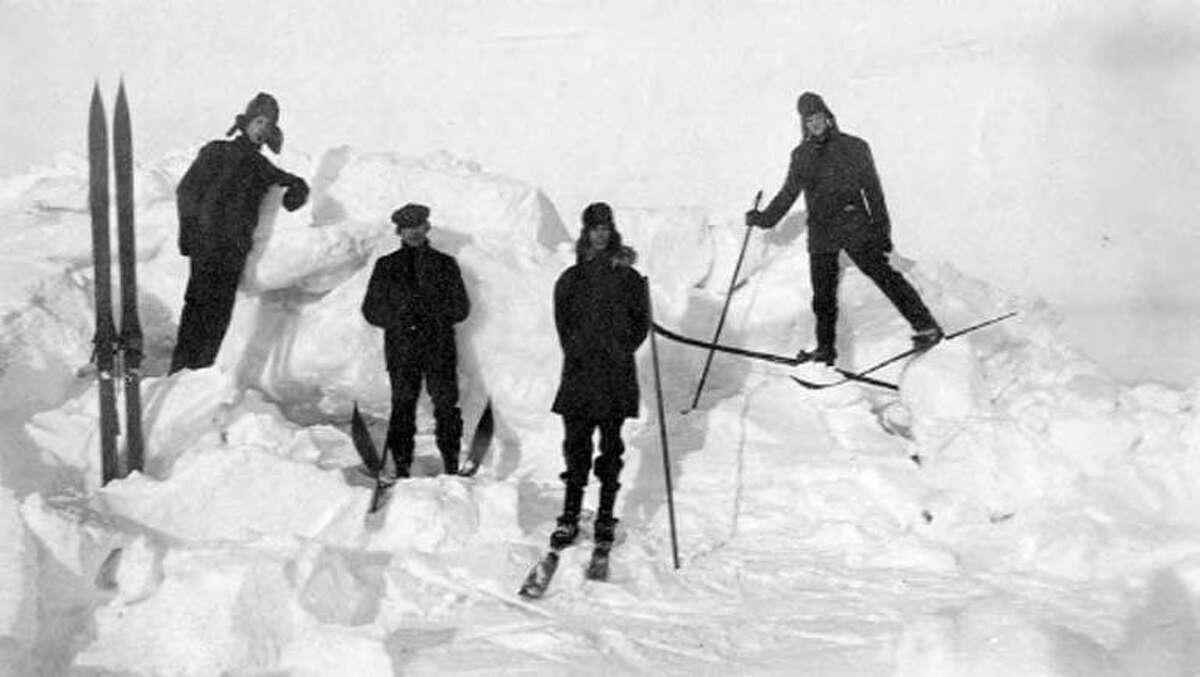 """""""Four skiers from the Nome Ski Club on hummock, vicinity of Nome, circa 1900-1920."""""""