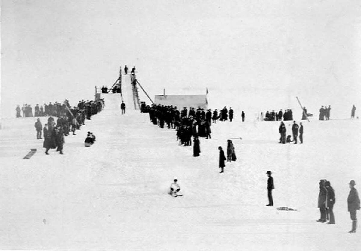 Another photo, taken between 1900 and 1920, shows ski and sled ramps with people lined up on either side to take their turn or watch the people coming down, near Nome, Alaska.