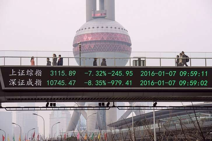 CORRECTION-CITY IN METADATA People walks along a pedestrian bridge with a screen showing stock market movements in Shanghai on January 7, 2016. China's market regulator on January 7 extended restrictions on big shareholders selling stocks, on whom a ban had been due to expire at the end of the week, as trade was suspended in the morning following a seven percent plunge.          AFP PHOTO   CHINA OUTSTR/AFP/Getty Images
