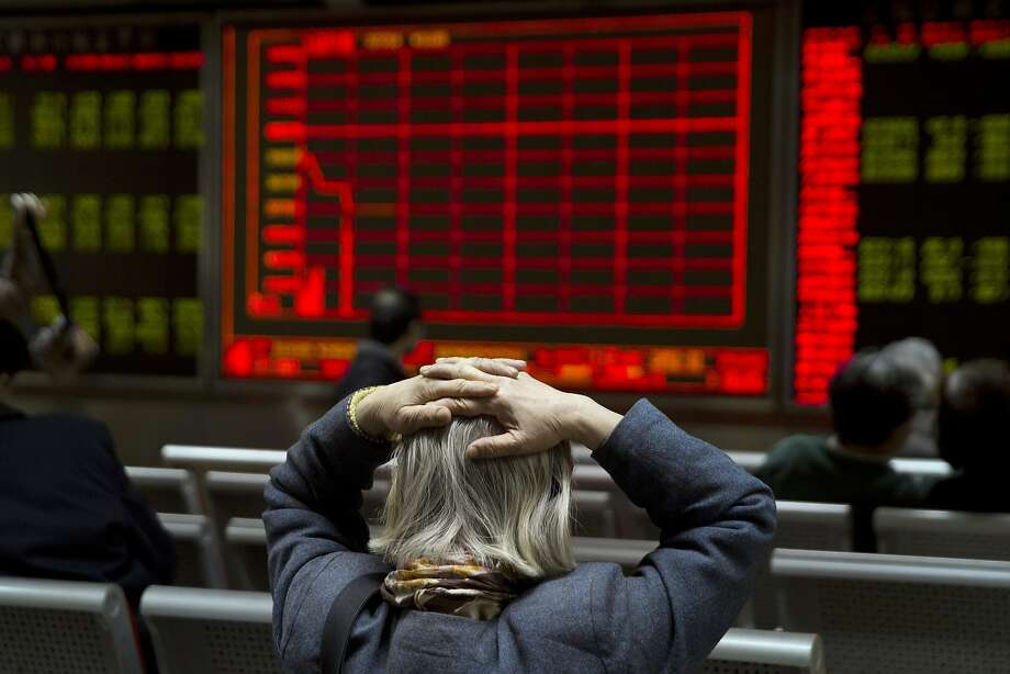 A woman in Beijing reacts to a display board that shows the plunge in the Shanghai composite index. Photo: Ng Han Guan, Associated Press