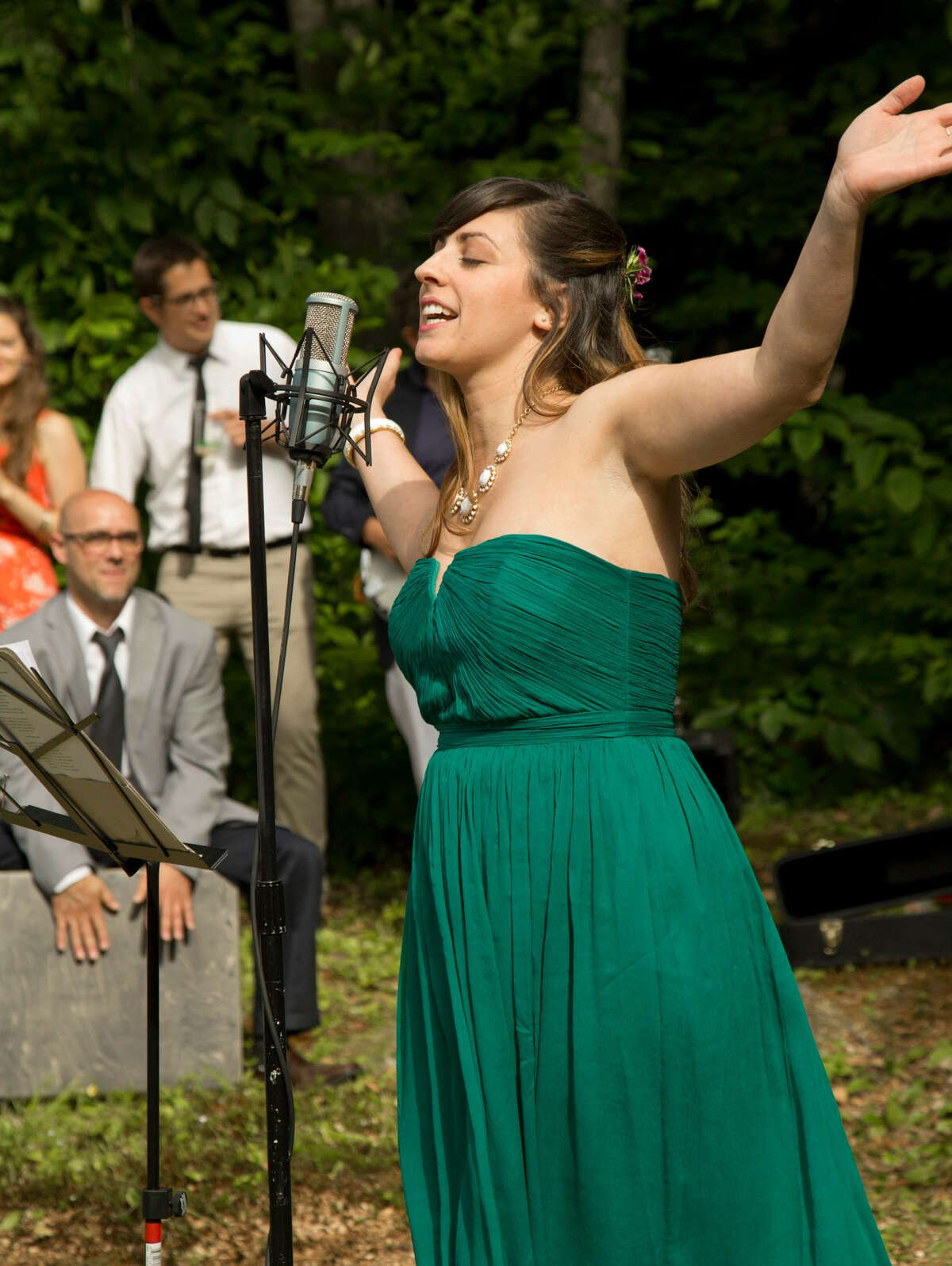 Emily Curro, this is a photo of her singing at her sister's wedding in Blandford, Mass. Photographer is Cindy Rzonca