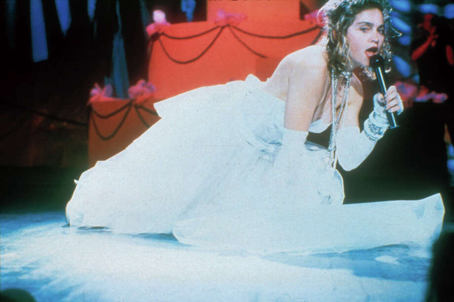 """Performing """"Like a Virgin"""" at the first MTV Video Music Awards show in Sept. 1984 at Radio City Music Hall in New York: Wearing the iconic white wedding dress bustier, """"Boy Toy"""" buckle, veil, garters and high heels, Madonna appeared atop a giant wedding cake prop and ended by writhing on the stage, creating an image as iconic as Jimi Hendrix climatically lighting his guitar on fire at the Monterey Pop Festival. Photo: Frank Micelotta Archive /Getty Images / 1984 Getty Images"""
