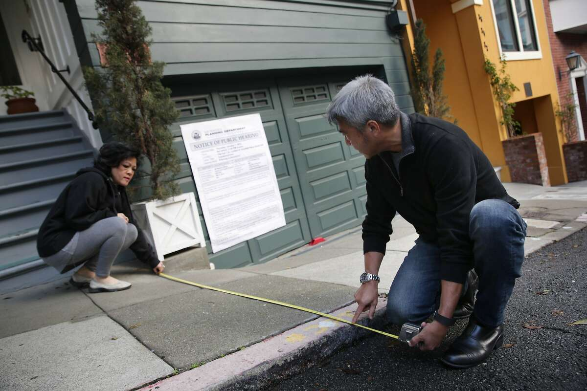 Alfonso Faustino (right) and his sister Irene Faustino (left) take measurements on Pleasant Street and the sidewalk for the upcoming public hearing of a neighbor who is trying to convert the 3-unit apt building into tourist hotel units (behind left) next to their home (behind right) on Thursday, January 7, 2015 in San Francisco, Calif.