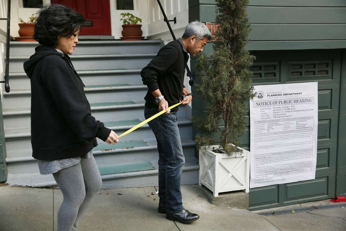 Alfonso Faustino (right) and his sister Irene Faustino (left) take measurements on Pleasant Street and the sidewalk for the upcoming public hearing of a neighbor who is trying to convert the 3-unit apt building into tourist hotel units (behind) next to their home (not shown) on Thursday, January 7, 2015 in San Francisco, Calif.