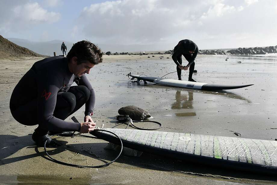 Travis Payne, left, of Pacifica, and Jamie Williams, of San Francisco get their boards ready on the beach as they prepare to surf at Maverick's in Half Moon Bay, CA Wednesday, January 7, 2016. Photo: Michael Short, Special To The Chronicle
