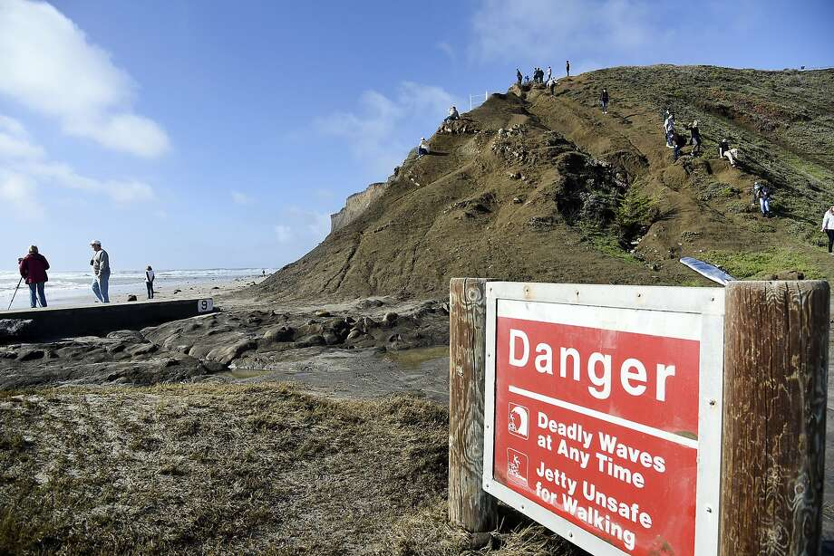 People watch waves break from the cliff above the beach at Maverick's in Half Moon Bay, CA Wednesday, January 7, 2016. Photo: Michael Short, Special To The Chronicle