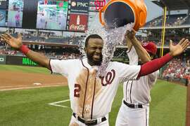 Washington Nationals Anthony Rendon dumps water on teammate Denard Span after he scored the winning run on a throwing error by Arizona Diamondback third baseman Jordan Pacheco during the ninth inning of a baseball game on Thursday, Aug. 21, 2014, in Washington. The Nationals defeated the Diamondbacks 1-0 to extend their winning streak to 10 games. (AP Photo/Evan Vucci)