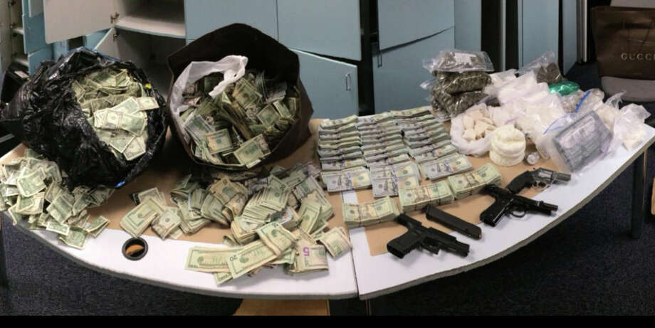 Guns, drugs and $405,000 in cash seized from Dwight Weems home are pictured in a law enforcement photo. Weems, 41, faces at least 15 years in federal prison. Photo: Department Of Justice