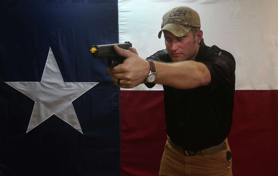 Josh Felker holds a handgun Thursday January 7, 2016 at the Lone Star Handgun Shooting Range in Converse, Texas. Felker and his wife Rebecca have run the business since 2004 and offer handgun training. Felker said while he may disagree with aspects of gun control, recent remarks made by President Obama will be good for his business. Photo: John Davenport, Staff / San Antonio Express-News / ©San Antonio Express-News/John Davenport