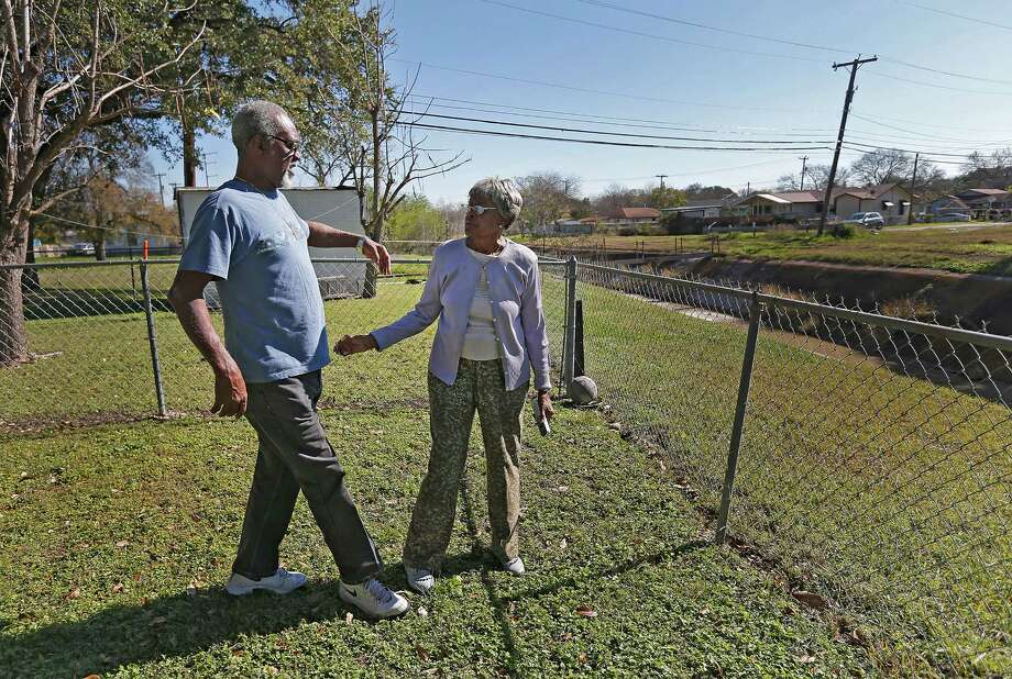 Foster Lamkin (left) goes to hug longtime East Side resident Minnie Applewhite in her backyard which faces Menger Creek as city and county officials gathered to kick off the start of drainage project on the creek on Thursday, Jan. 7, 2016. The groundbreaking ceremony marked the transformation of Menger Creek into a linear park as part of a flood control project via the 2012 Bond Program. Among the improvements along the creek will be a new span bridge at Rio Grande Street, culvert improvements, a new pedestrian bridge and ADA compliant ramps. The linear park will have shaded canopies, playground equipment, a pavilion, a basketball court and a walking trail. Applewhite has lived near the creek for about 60 years and looks forward to the new improvements to the area. (Kin Man Hui/San Antonio Express-News) Photo: Kin Man Hui, Staff / San Antonio Express-News / ©2016 San Antonio Express-News
