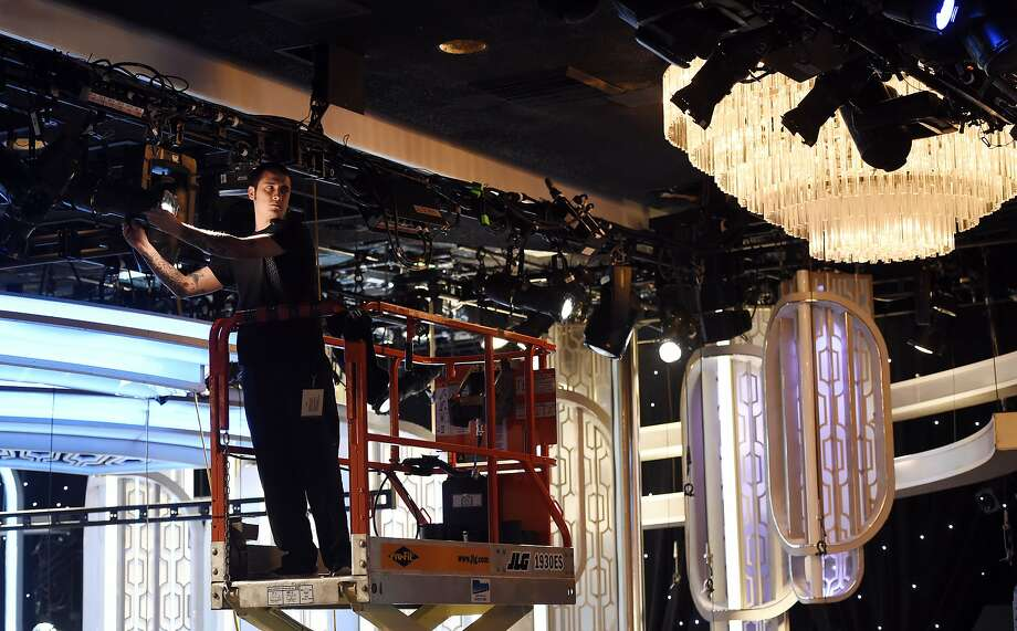 Crew member Chris Lopez adjusts lights in the ballroom during preview day for the 73rd Annual Golden Globe Awards extravaganza at the Beverly Hilton on Sunday. Photo: Chris Pizzello, Associated Press