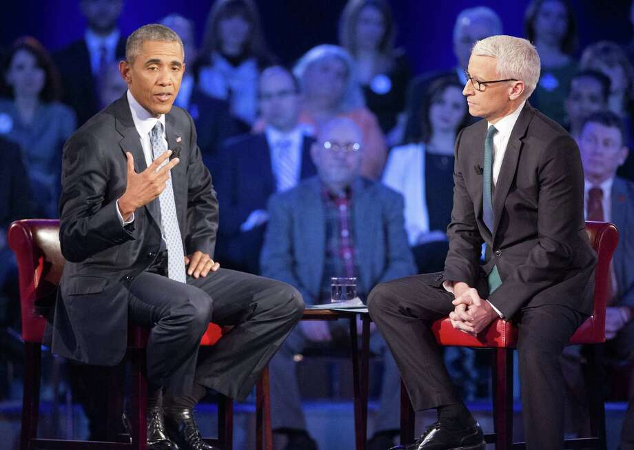 President Barack Obama, left, speaks during a CNN televised town hall meeting hosted by Anderson Cooper, right, at George Mason University in Fairfax, Va., Thursday, Jan. 7, 2016. Obama's proposals to tighten gun controls rules may not accomplish his goal of keeping guns out of the hands of would-be criminals and those who aren't legally allowed to buy a weapon. In short, that's because the conditions he is changing by executive action are murkier than he made them out to be. Photo: Pablo Martinez Monsivais, AP / AP