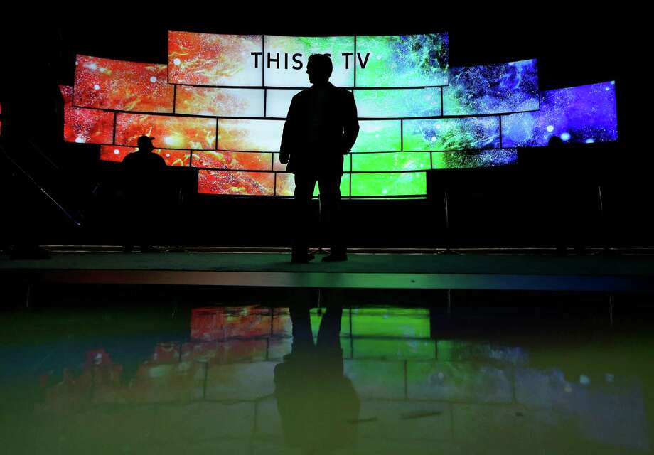 A man checks out Samsung SUHD TVs at CES International in Las Vegas. Samsung's new smart TVs will have built-in smart-home capabilities, negating the need to buy a hub to get started on a quest for a fully automated home. Photo: Gregory Bull /Associated Press / AP