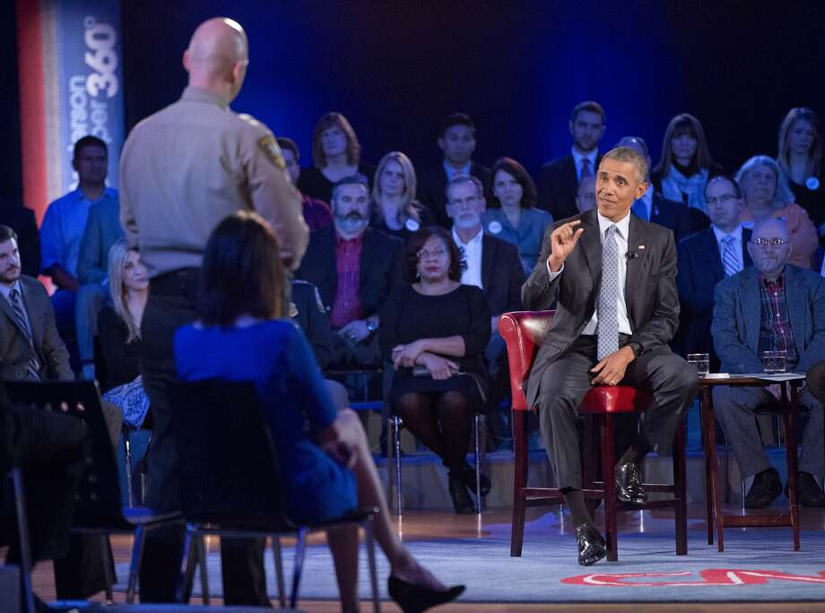 President Obama answers questions from Sheriff Paul Babeu (left standing) of Pimal County, Ariz., during a CNN televised town hall meeting at George Mason University in Fairfax, Va. Photo: Pablo Martinez Monsivais, Associated Press