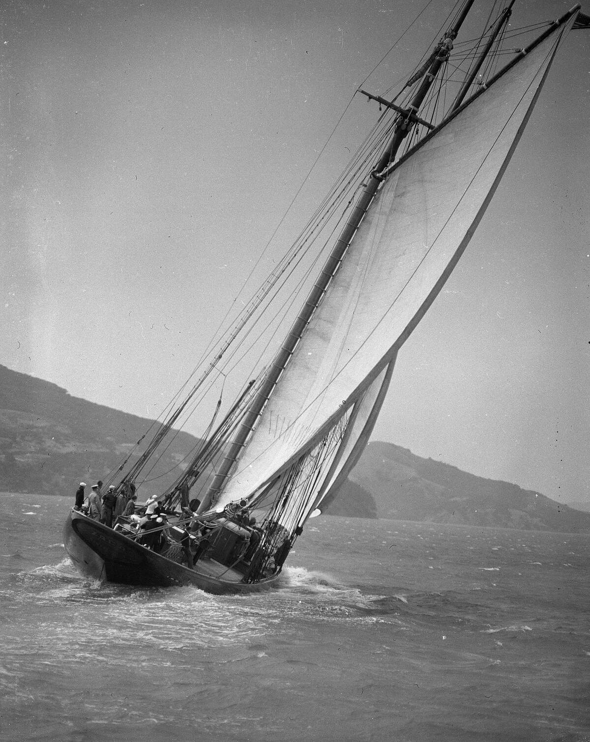 Schooner Zaca, August 1942, in WWII service with the US Navy. The 118' schooner was designed by Garland Rotch for Templeton Crocker, grandson of the railroad baron. She was built in Sausalito, California by the Nunes Brothers Boat and Ways Co. and launched in 1930. Crocker, with Rotch as captain, took the vessel around the world. In 1942 the Navy took the schooner for defense purposes. After the war Errol Flynn owned the boat and the vessel was know for wild parties. After Flynn's death in 1959, the boat deteriorated in the Mediterranean area but was finally saved and elegantly restored by Italian Roberto Memmo and home ported in Monaco. Scanned Chronicle file negatives, one packet dated August, 1942