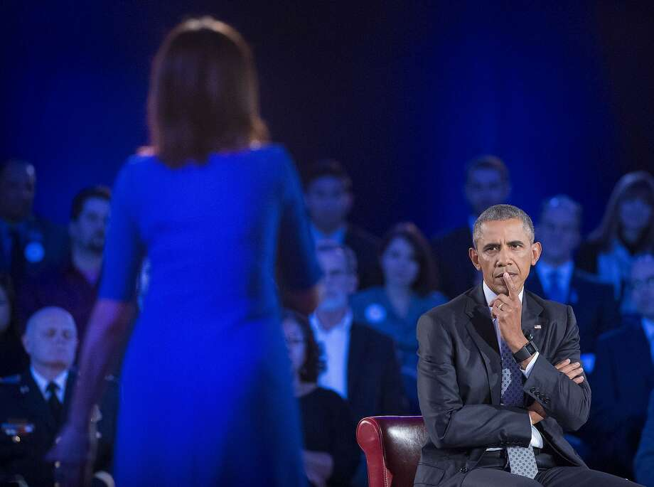 President Barack Obama, right, listens to a question from Taya Kyle, left, widow of U.S. Navy SEAL Chris Kyle, during a CNN televised town hall meeting hosted by Anderson Cooper at George Mason University in Fairfax, Va., Thursday, Jan. 7, 2016. Obama's proposals to tighten gun controls rules may not accomplish his goal of keeping guns out of the hands of would-be criminals and those who aren't legally allowed to buy a weapon. In short, that's because the conditions he is changing by executive action are murkier than he made them out to be. (AP Photo/Pablo Martinez Monsivais) Photo: Pablo Martinez Monsivais, Associated Press