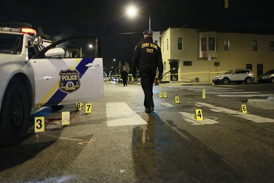 An investigator examines the scene of what the Philadelphia police commissioner called an attempted assassination. Photo: Joseph Kaczmarek, Associated Press