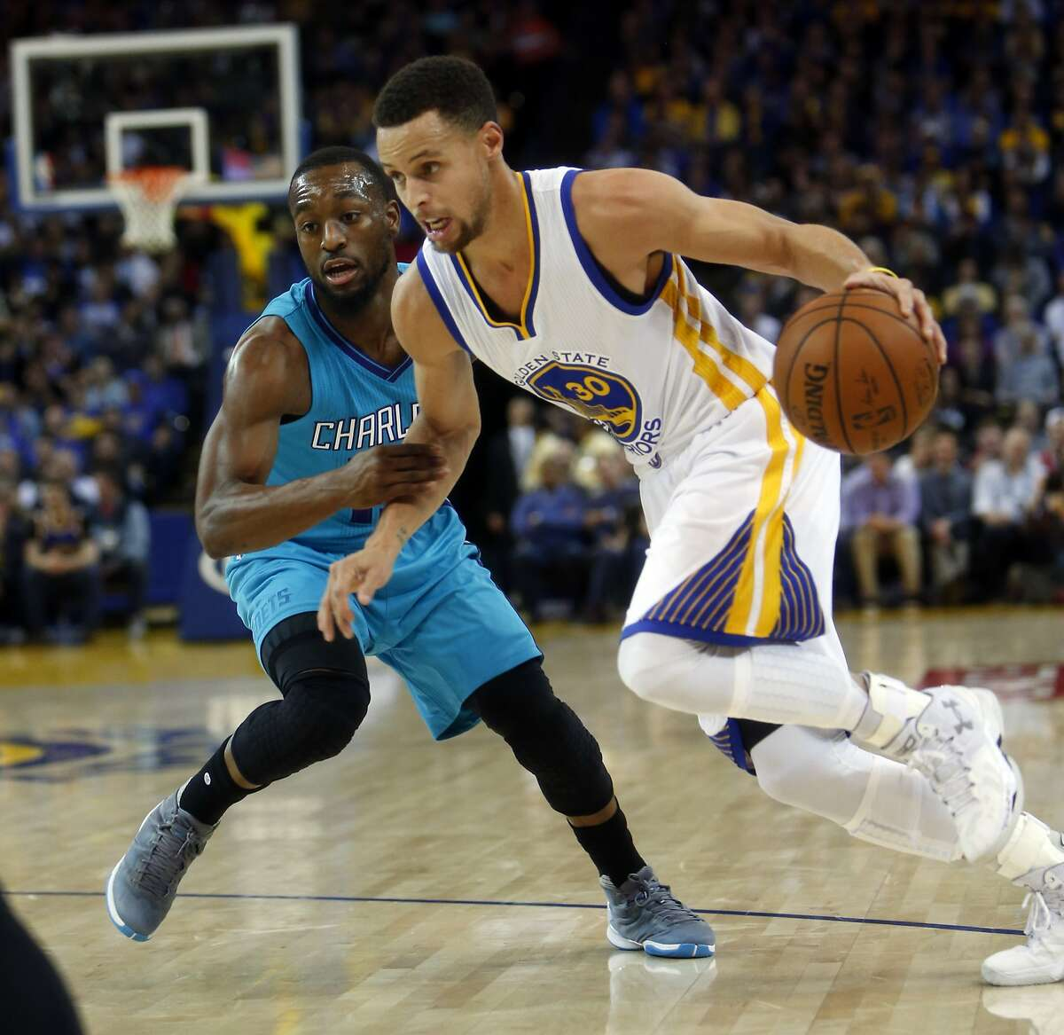 Golden State Warriors' Stephen Curry drives against Charlotte Hornets' Kemba Walker in 2nd quarter during NBA game at Oracle Arena in Oakland, Calif., on Monday, January 4, 2016.