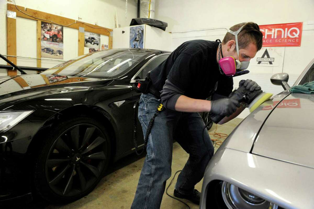 Kevin Awalt polishes the paint on a customer's car Wednesday, January 6, 2016. Awalt, 36, of Brookfield is the owner of Arkham Shine, an auto detailing shop in New Milford.