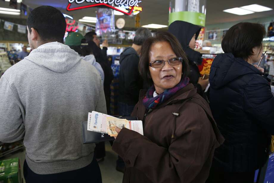 Rosalina Stebbins glances back at the end of the line while waiting to buy tickets for Saturday night's Powerball lottery draw at Kavanagh Liquors in San Lorenzo, Calif. on Friday, Jan. 8, 2016. A steady line of customers waited in a line that snaked through the store for the lottery draw with an estimated $800 million on the line. Photo: Paul Chinn, The Chronicle