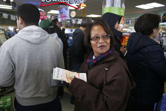 Rosalina Stebbins glances back at the end of the line while waiting to buy tickets for tomorrow night's Powerball lottery draw at Kavanagh Liquors in San Lorenzo, Calif. on Friday, Jan. 8, 2016. A steady line of customers waited in a line that snaked through the store for tomorrow night's lottery draw with an estimated $800 million on the line.