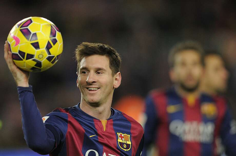 FILE - This is a Sunday, Dec. 7, 2014 file photo of FC Barcelona's Lionel Messi holding the ball after scoring a hat-trick in the Spanish La Liga soccer match between FC Barcelona and Espanyol at the Camp Nou stadium in Barcelona, Spain. The 2015 Ballon d'Or award is on Monday Jan. 11, 2016 in Zurich and Messi is strongly favored to be named FIFA best player for a fifth time. Ronaldo has won it three times including the past two years. Messi's Barcelona teammate Neymar is the other candidate. (AP Photo/Manu Fernandez, File) Photo: Manu Fernandez, Associated Press