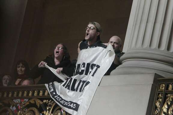 Protesters are removed as they hold a banner during the Inauguration of Mayor Lee  at City Hall on Friday, January 8, 2015 in San Francisco, Calif.