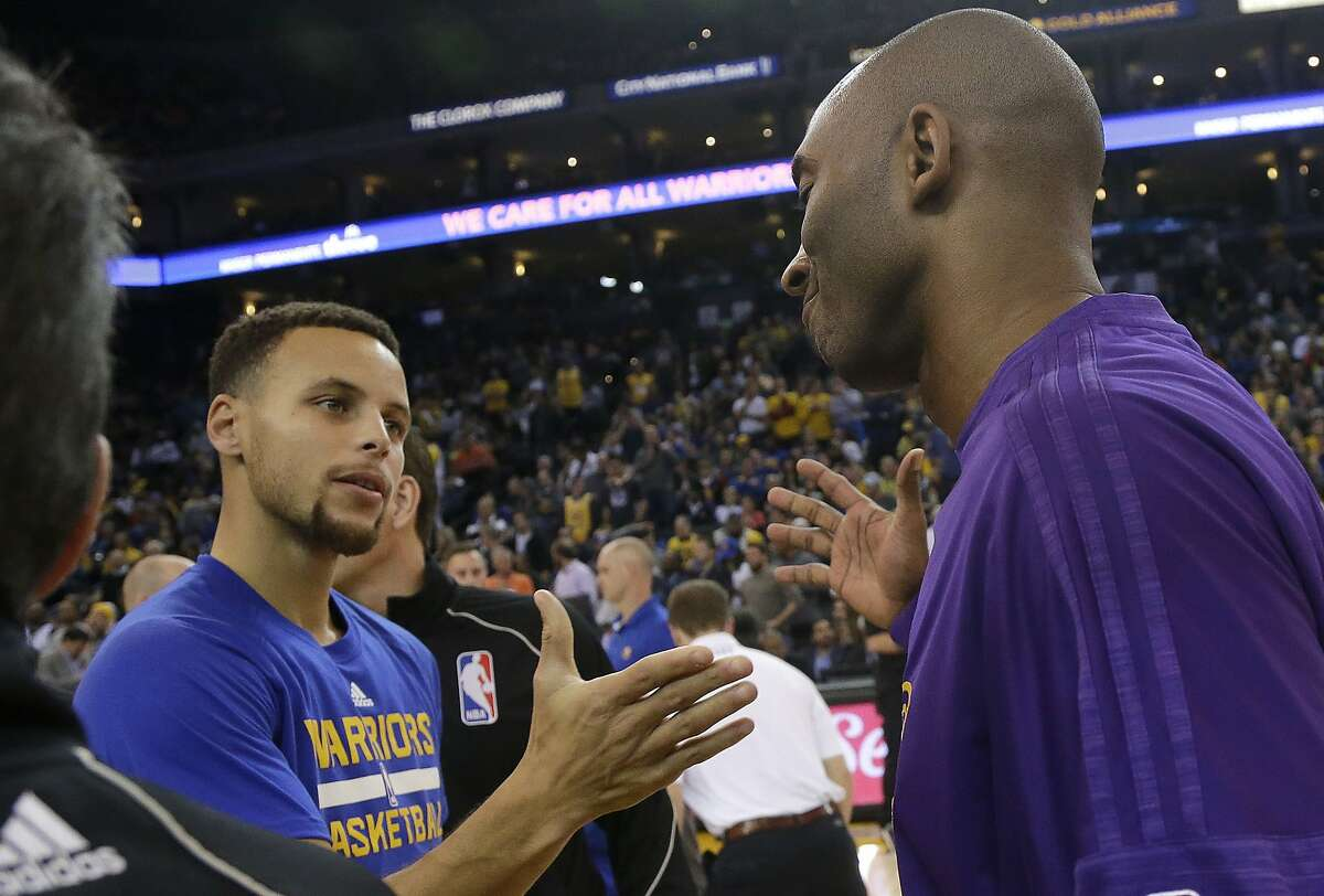 Golden State Warriors guard Stephen Curry, left, greets Los Angeles Lakers guard Kobe Bryant before an NBA basketball game in Oakland, Calif., Tuesday, Nov. 24, 2015. (AP Photo/Jeff Chiu)