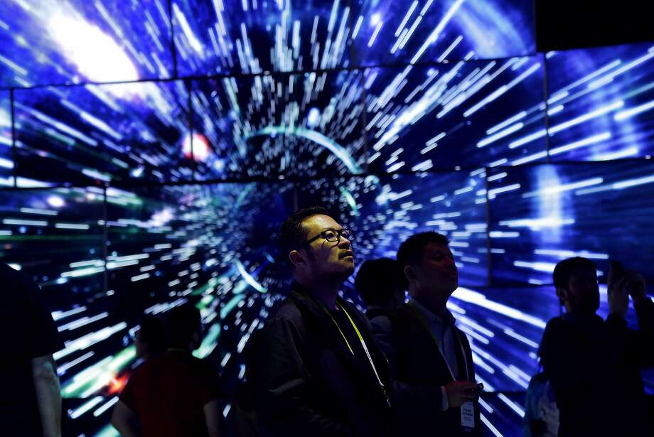 Bao Truong looks at a display of Samsung SUHD Quantum dot display TVs at the Samsung booth during CES International, Friday, Jan. 8, 2016, in Las Vegas. (AP Photo/Gregory Bull) Photo: Gregory Bull, Associated Press
