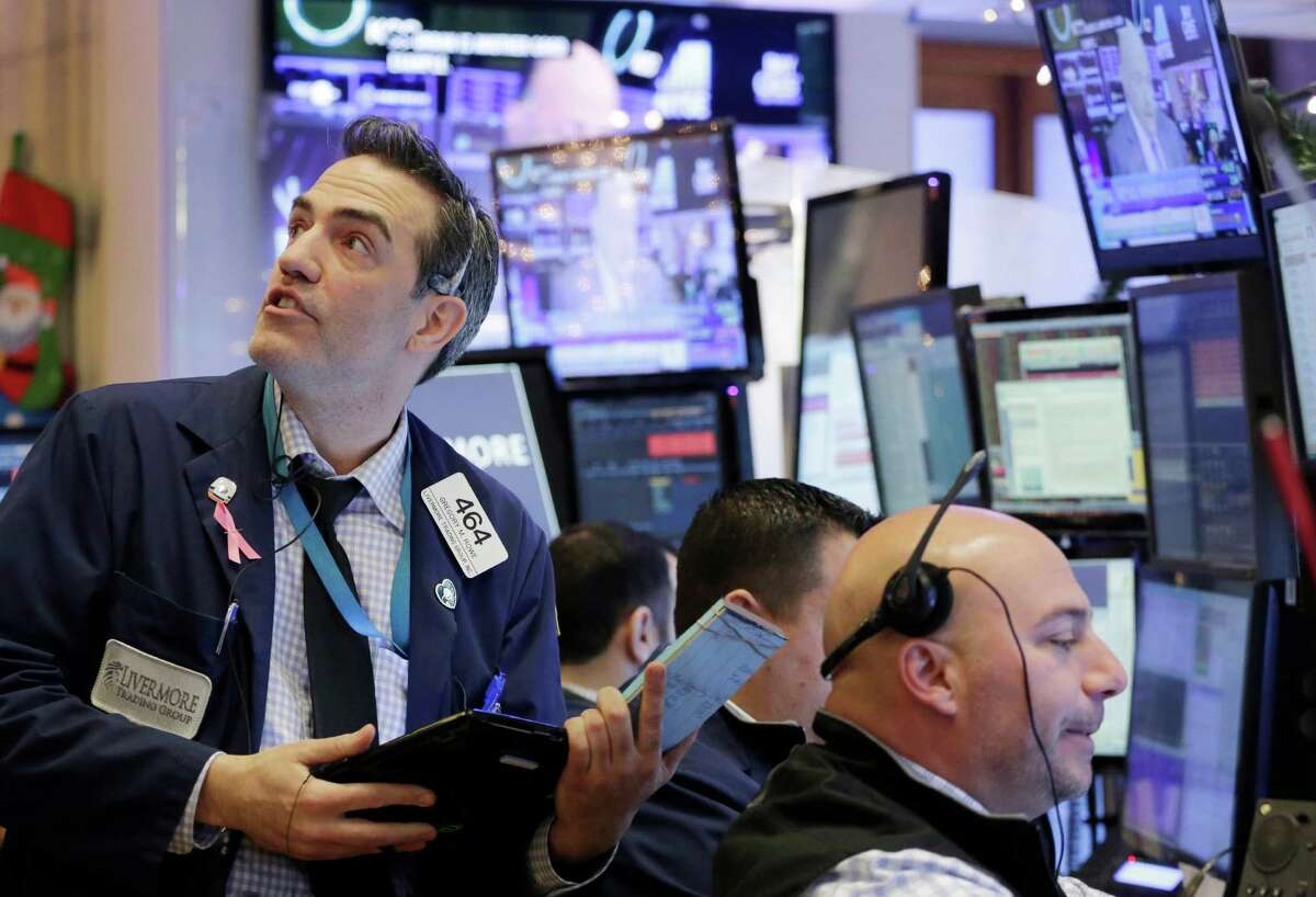 Gregory Rowe, left, with Livermore Trading Group, keeps an eye on stock prices at the New York Stock Exchange, Friday, Jan. 8, 2016. A rebound in Chinese stocks helped shore up the mood in global stock markets Friday in the run-up to U.S. jobs data. (AP Photo/Mark Lennihan) ORG XMIT: NYML110
