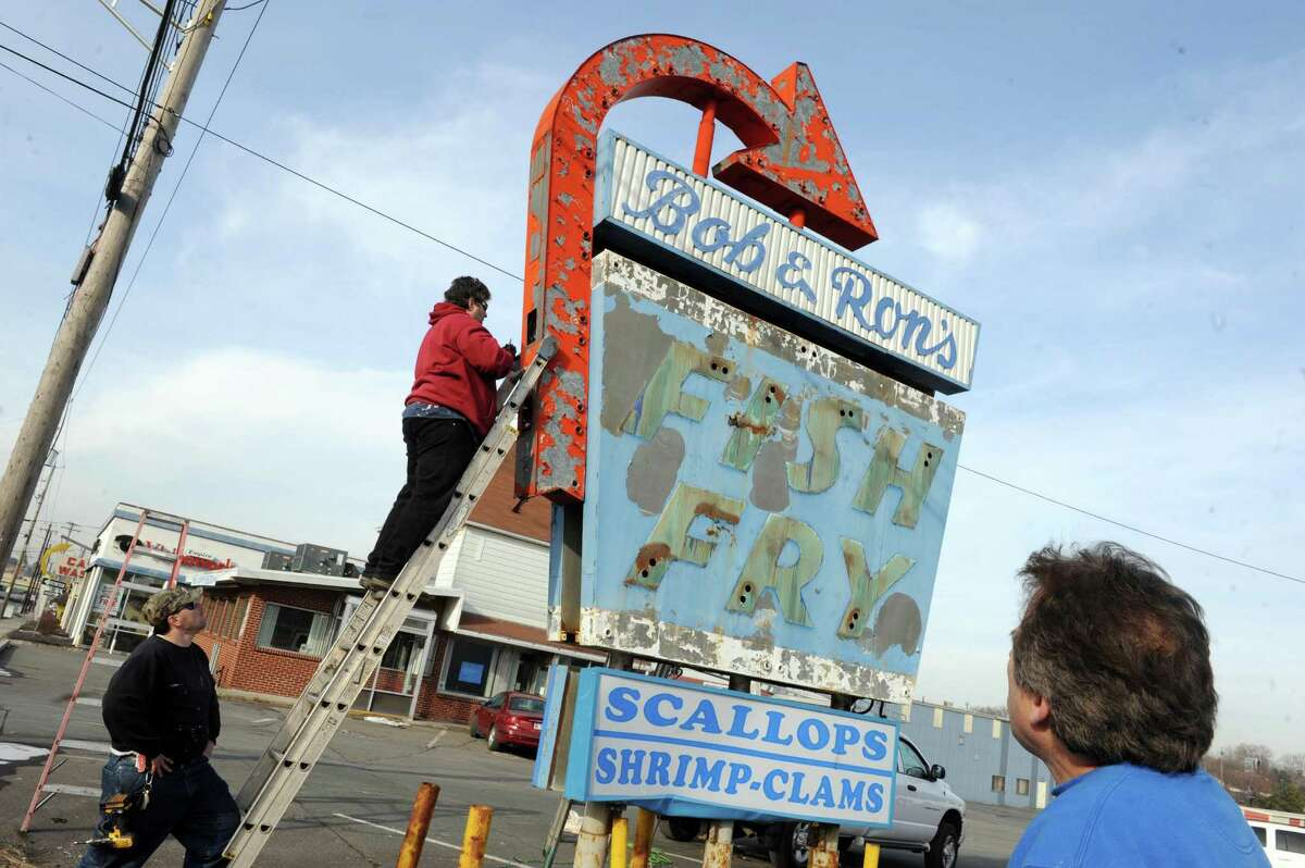 Historic sign collector Leon Johnson, right, of Norwood, New Jersey supervises the disassembly of the Bob & Rons Fish Fry sign on Central Avenue Friday Jan. 8, 2016 in Albany, N.Y. Johnson bought the sign for $900 during an online auction. (Michael P. Farrell/Times Union)