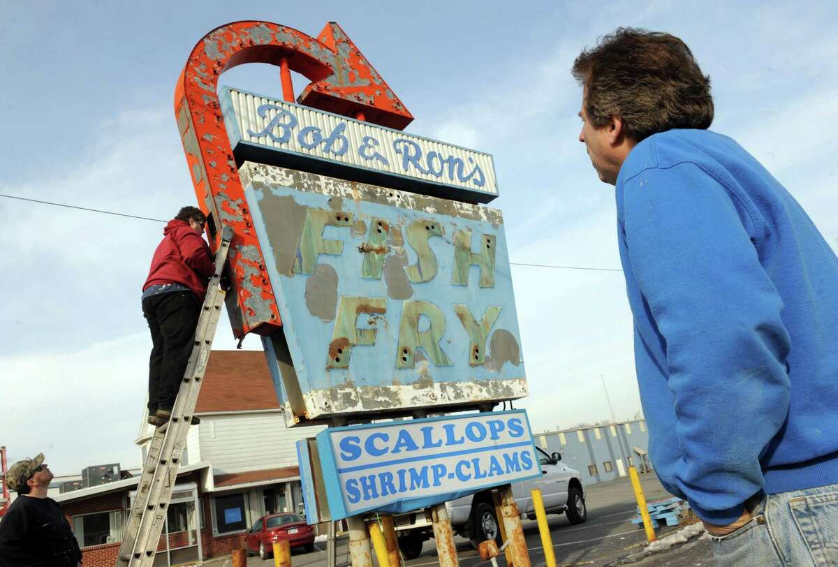 Historic sign collector Leon Johnson, right, of Norwood, New Jersey supervises the disassembly of the Bob & Ron's Fish Fry sign on Central Avenue Friday Jan. 8, 2016 in Albany, N.Y. Johnson bought the sign for $900 during an online auction. (Michael P. Farrell/Times Union)