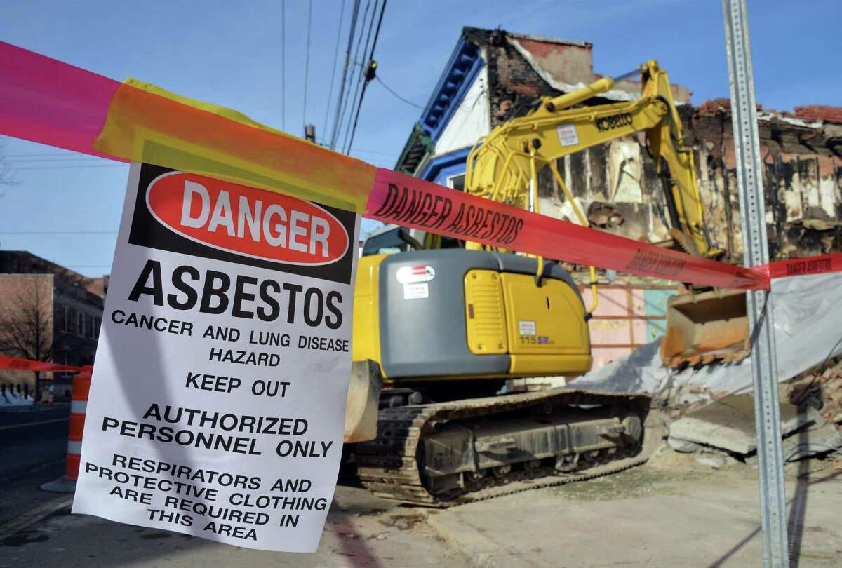 Asbestos warnings are posted as Jackson Demolition crews prepare to remove the pile of debris left from a fire that tore through 31-33 Broad St. last month Friday Jan. 8, 2016 in Waterford, NY. (John Carl D'Annibale / Times Union)