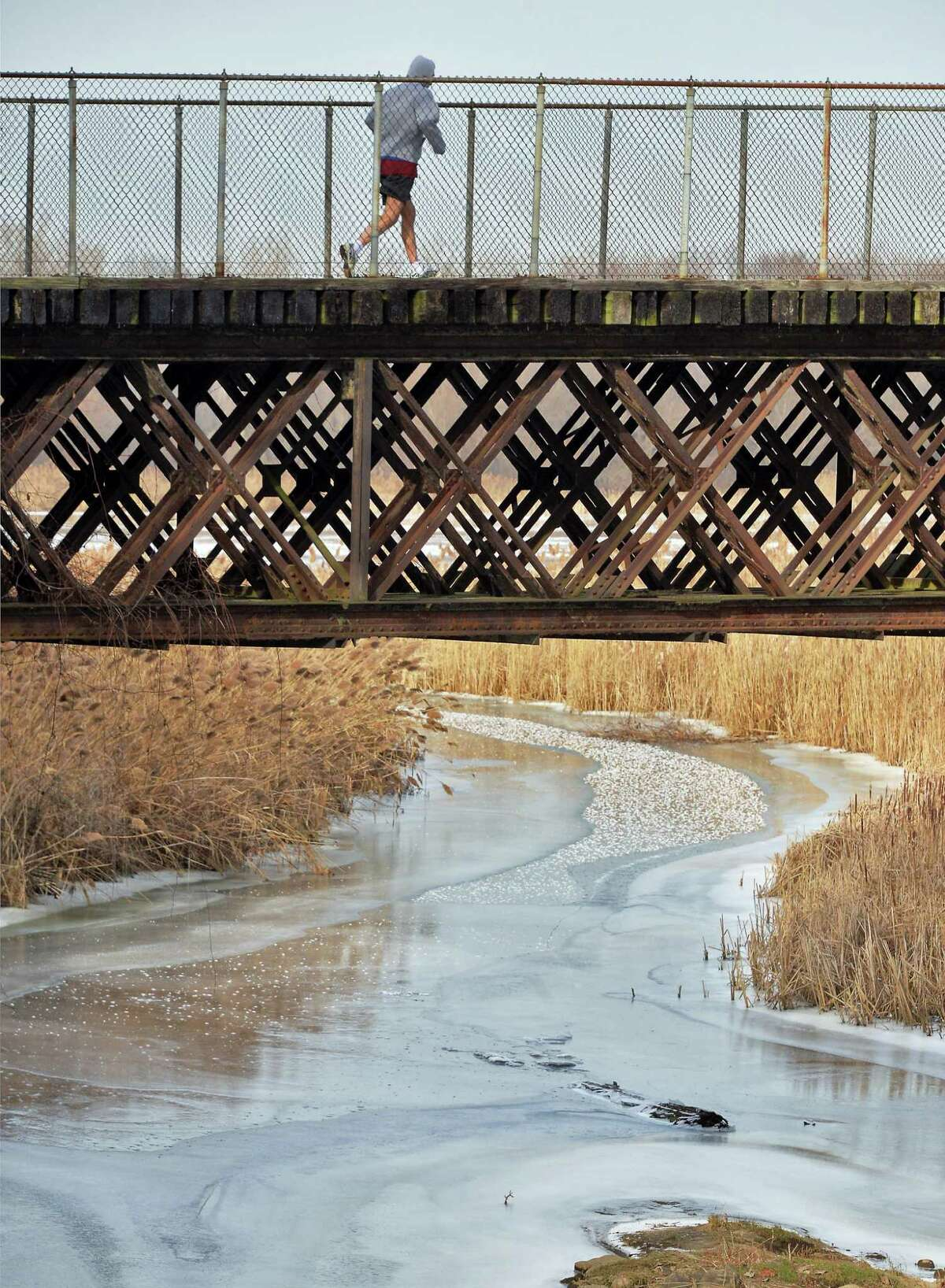 A lone runner crosses a bridge over a frozen stream along the bike path Friday Jan. 8, 2016 in Colonie, NY. (John Carl D'Annibale / Times Union)
