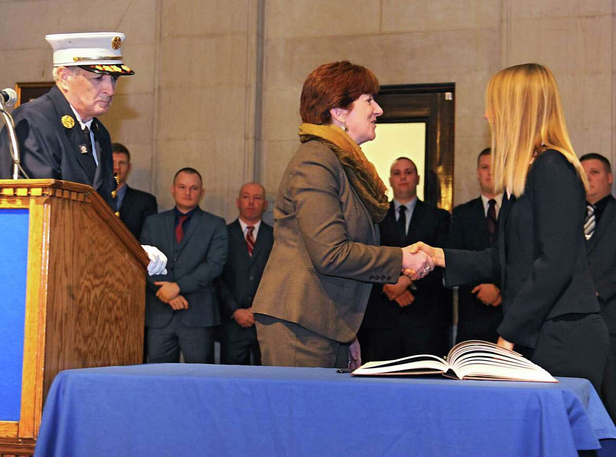 Albany Mayor Kathy Sheehan, center, shakes hands with new firefighter Erin Engstrom after she signed a book during a swearing in ceremony in at City Hall Friday, Jan. 8, 2016 in Albany, N.Y. Erin is the first new female firefighter in 18 years. Fire chief, Warren Abriel, Jr. watches at left. (Lori Van Buren / Times Union)