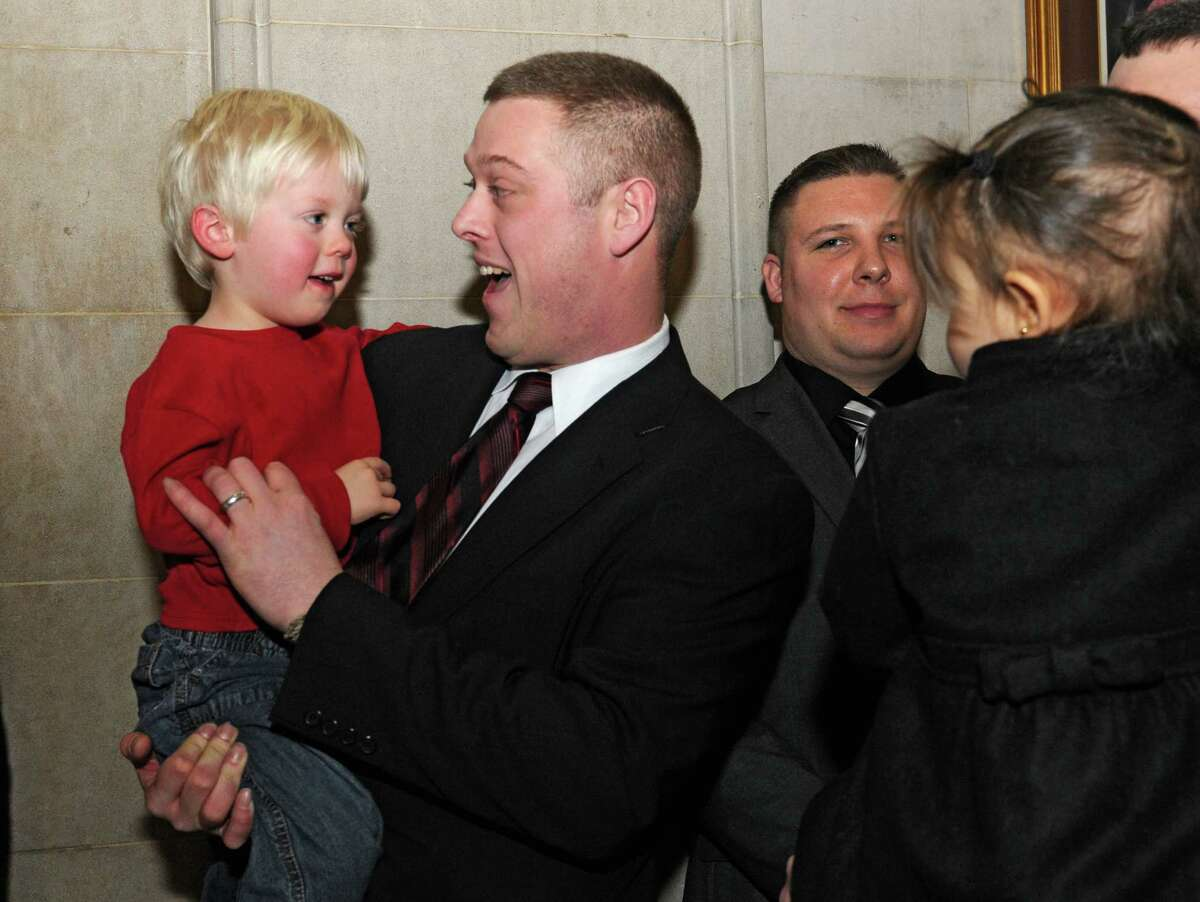 New firefighter Kyle Eckert gets a hug from his son Gavin, 3, after Kyle was sworn in at City Hall Friday, Jan. 8, 2016 in Albany, N.Y. (Lori Van Buren / Times Union)