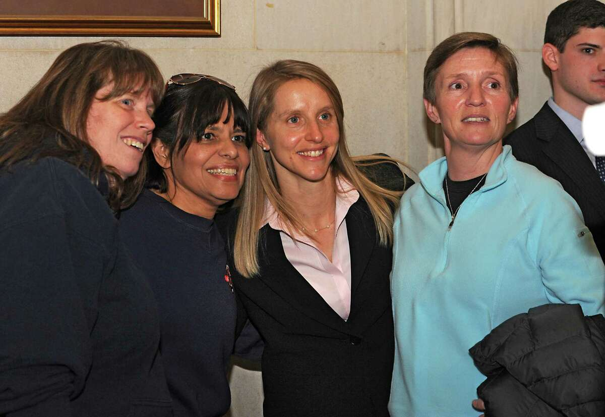 Erin Engstrom, third from left, gets her photo taken with Albany firefighters Maria Walker, left, Zory Pineiro, second from left and retired firefighter Nancy Horn, right, after being sworn in at City Hall Friday, Jan. 8, 2016 in Albany, N.Y. Engstrom is the first new female firefighter hired in 18 years. (Lori Van Buren / Times Union)