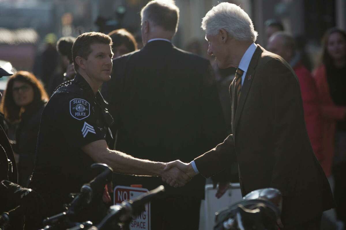 President Bill Clinton shakes hands with a Seattle PD officer on his way into a fundraiser for his wife's campaign at the Century Ballroom in Capitol Hill on Friday, Jan. 8, 2016.