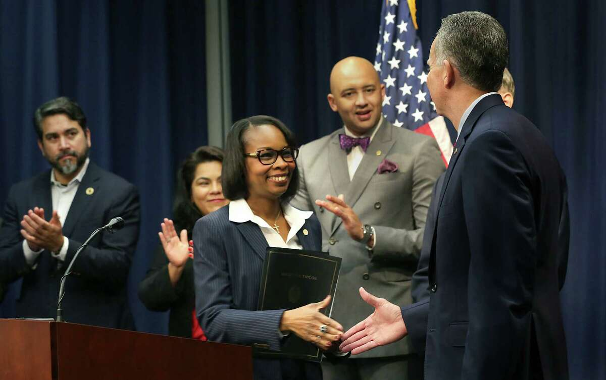 Mayor Ivy Taylor greets USAA CEO Stuart Parker during an announcement that the company is donating $2.1 million to help end veterans' homelessness in the city.