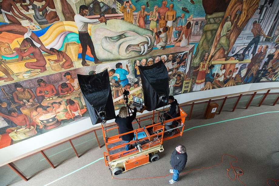"Cultural Heritage Imaging directors Carla Schroer (above left) and Marlin Lum (above right) photograph Diego Rivera's ""The Pan American Unity Mural"" at San Francisco City College on December 22, 2015. The 75-year-old painting located on the campus for decades is being photographed and documented in high resolution 2D and 3D digital formats to help it be preserved for future generations. Photo: JOSH EDELSON / SAN FRANCISCO CHR"