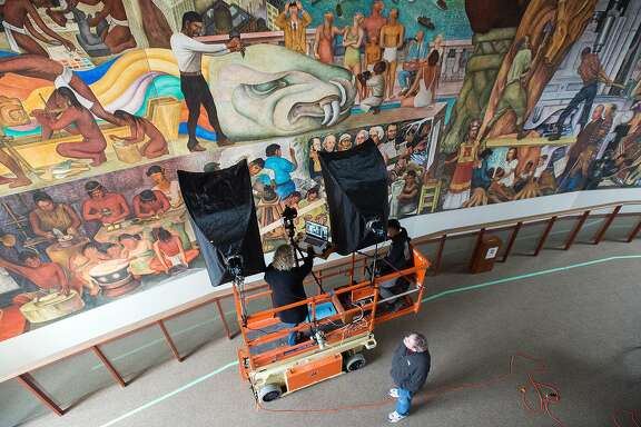 "Cultural Heritage Imaging directors Carla Schroer (above left) and Marlin Lum (above right) photograph Diego Rivera's ""The Pan American Unity Mural"" at San Francisco City College on December 22, 2015. The 75-year-old painting located on the campus for decades is being photographed and documented in high resolution 2D and 3D digital formats to help it be preserved for future generations."