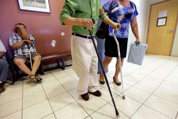 In this file photo shows a man using two canes in the waiting area at Nuestra Clinica Del Valle in San Juan, Texas. About 85 percent of those served at the clinic are uninsured. Without Medicaid expansion, the states working poor will continue relying on emergency rooms — the most costly treatment option — instead of primary care doctors.