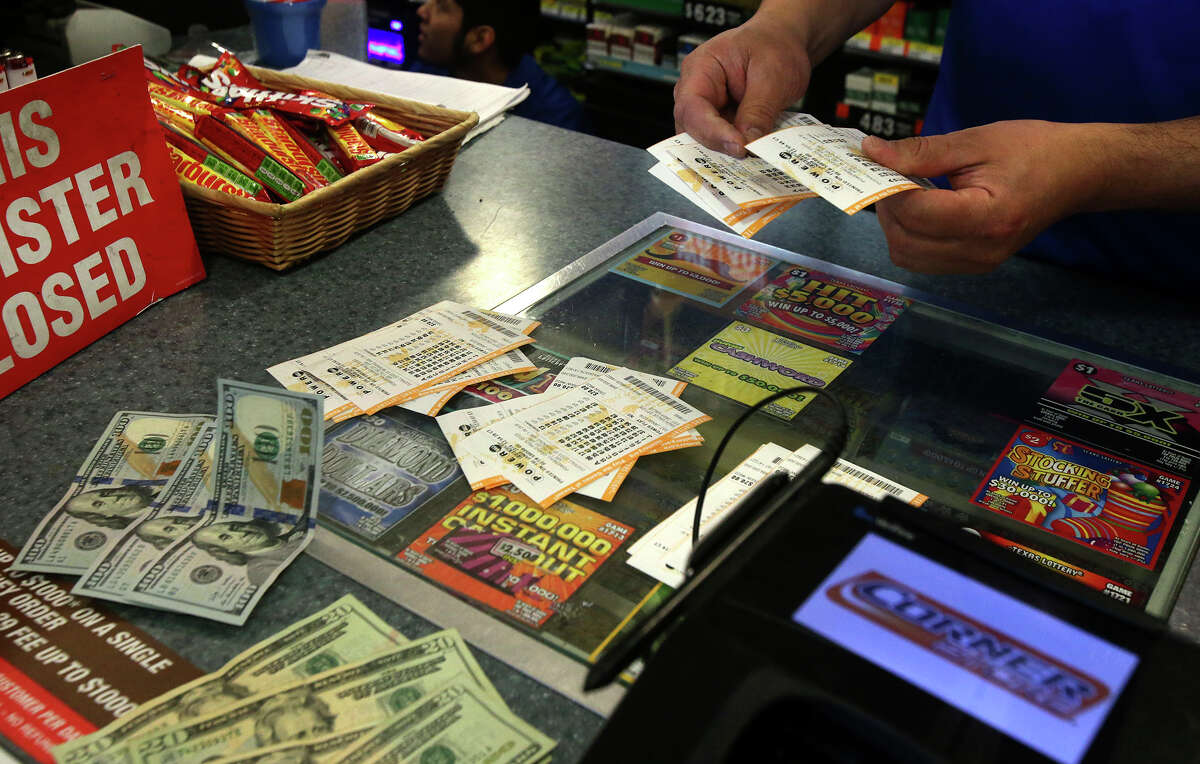 A clerk sorts $390 worth of Powerball tickets Friday at the Corner Store at UTSA Boulevard and Interstate 10. The tickets were purchased by Lamar Sales, a graduate student at UTSA who purchased the tickets for a group of fellow students. As of Friday, the Powerball jackport is an estimated $800 million.