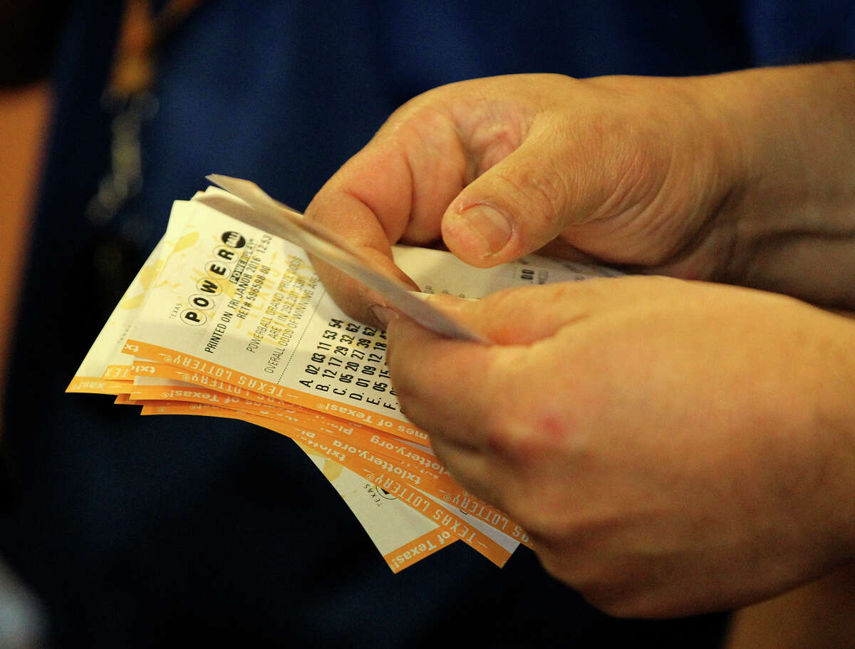 A clerk sorts Powerball tickets Friday at the Corner Store at UTSA Boulevard and Interstate 10. As of Friday, the Powerball jackport is an estimated $800 million.