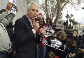 San Francisco District Attorney George Gascon, foreground, speaks in front protesters in front of the Hall of Justice in San Francisco, Friday, Dec. 18, 2015. Demonstrators gathered in front of San Francisco's criminal courthouse to protest the police shooting death of Mario Woods, the knife-wielding stabbing suspect shot dead in the city's Bayview neighborhood earlier this month, and to demand the dismissal of police chief Greg Suhr. (AP Photo/Janie Har)