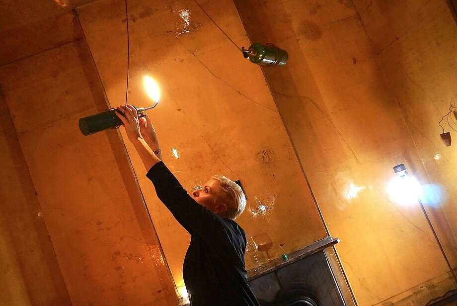 500 Capp Street Foundation Director Carlie Wilmans lights a chandelier artwork by the late artist David Ireland during a dinner at his former home. Nov 2015. Photo: Catherine Bigelow, Special To The Chronicle