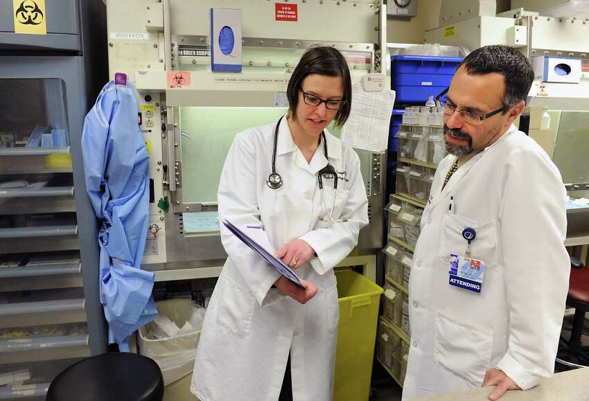 Lung cancer specialist Dr. Makenzi Evangelist of New York Oncology Hematology (NYOH), left, goes over a chart with Dr. Ira Zackon, president of NYOH and hematologist, in the pharmacy lab at NYOH in Albany Medical Center on Friday, Jan. 8, 2016 in Albany, N.Y. (Lori Van Buren / Times Union)