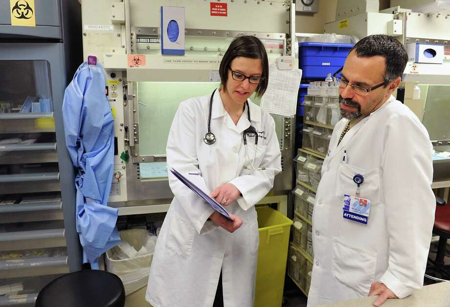 Lung cancer specialist Dr. Makenzi Evangelist of New York Oncology Hematology (NYOH), left, goes over a chart with Dr. Ira Zackon, president of NYOH and hematologist, in the pharmacy lab at NYOH in Albany Medical Center on Friday, Jan. 8, 2016 in Albany, N.Y.  (Lori Van Buren / Times Union) Photo: Lori Van Buren / 10034928A