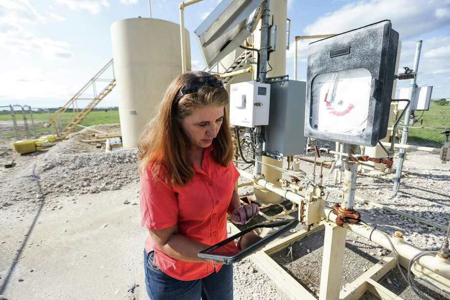 Using an application created by San Antonio-based WellAware, Welder Exploration & Production Inc. employee Gaye Hester compares the readout on the well and tank to the levels on the app. By attaching a sensor to the collection tanks, oil and water levels can be tracked and measured remotely. Photo: Michael Ciaglo /Houston Chronicle / © 2015  Houston Chronicle