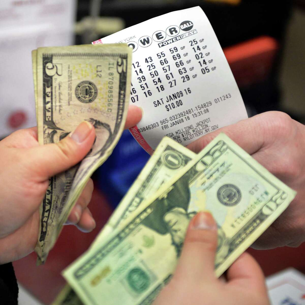 Store manager Jay Letourneau sells Powerball lottery tickets to a customer at the Stewart's store at the corner of Osbourne and Sand Creek Road Friday Jan. 8, 2016 in Colonie, NY. (John Carl D'Annibale / Times Union)